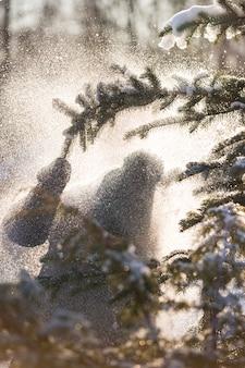 Close-up van een jongetje dat een boomtak trekt met sneeuw en sneeuw valt op hem