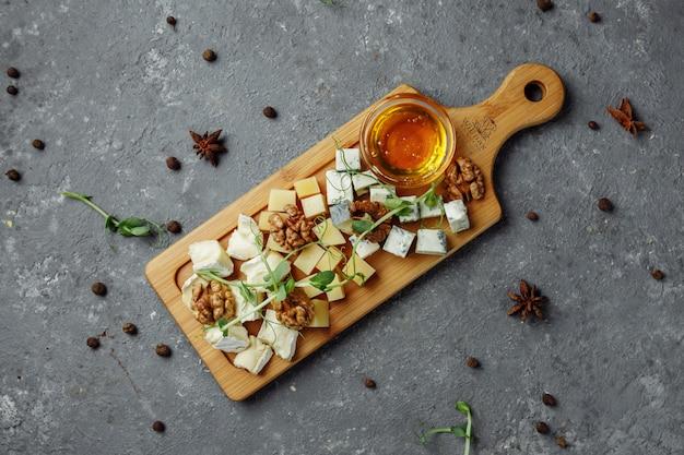 Close-up van een kaasplateau. 4 soorten kaas, zachte witte brie, camembert, halfzachte briques, blauw, roquefort, harde kaas