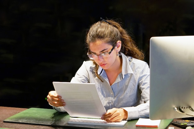 Close-up van een kantoormedewerker leest negatief nieuws in een brief. het geschokte meisje was verrast door het ontslag uit het bedrijf.