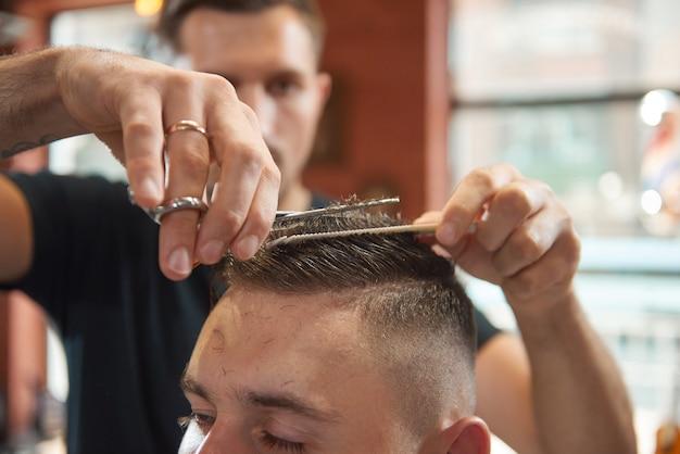 Close-up van een kapper met behulp van een schaar die haar van zijn mannelijke klant snijdt