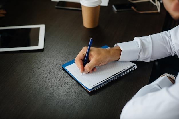 Close-up van een kerel die in een notitieboekje zijn ideeën en gedachten schrijft