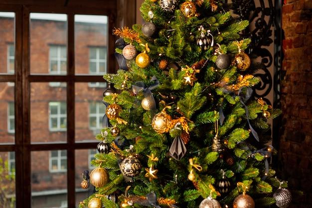 Close-up van een kerstboom versierd met gouden ballen en blauwe bogen. kerst vakantie concept