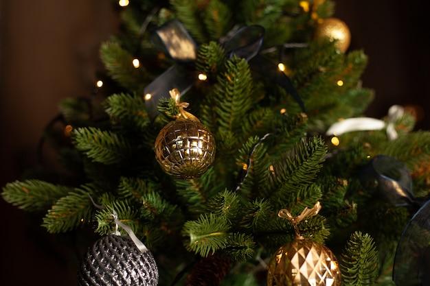 Close-up van een kerstboom versierd met gouden ballen en blauwe strikken. kerst vakantie concept.