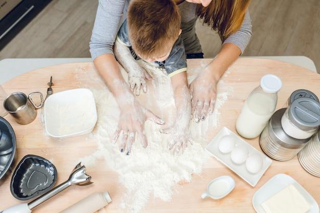 Close-up van een keukentafel met twee paar handen: moeder en zoon met keukenspullen op tafel.