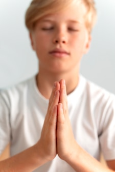 Close-up van een kind dat binnenshuis mediteert