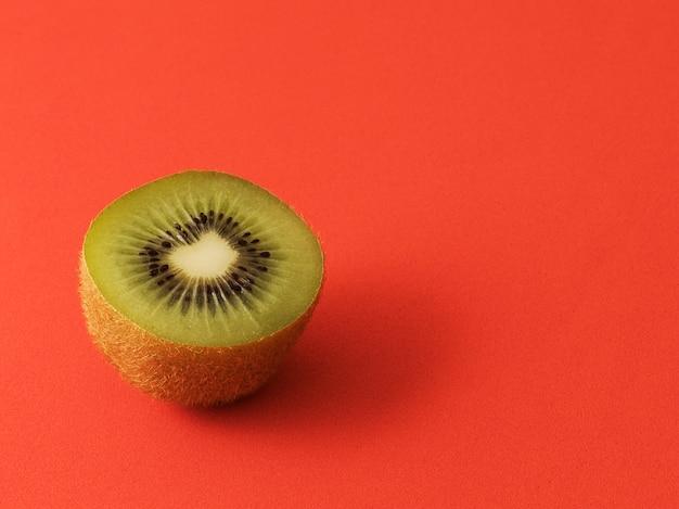 Close-up van een kiwi in tweeën gesneden geïsoleerd op een rode achtergrond