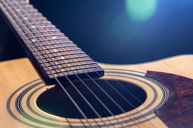 Close-up van een klassieke akoestische gitaar op een onscherpe achtergrond met bokeh.