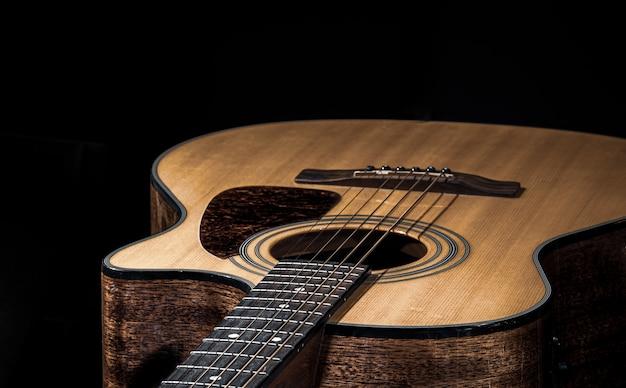Close-up van een klassieke akoestische gitaar op een zwarte achtergrond.