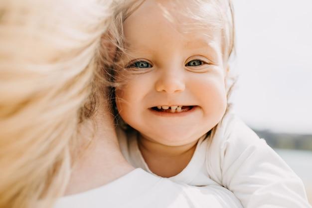 Close-up van een klein meisje dat lacht en haar eerste tanden laat groeien