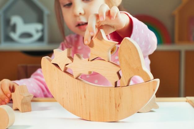 Close up van een klein meisje dat speelt met houten speelgoed galaxy balancer op tafel in de kinderkamer