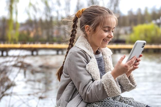 Close-up van een klein meisje met een telefoon in haar handen op de achtergrond van de natuur.