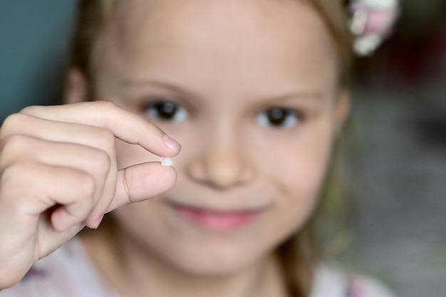 Close-up van een klein meisje met gevallen melktand in haar hand problemen met tanden pediatrische dentis