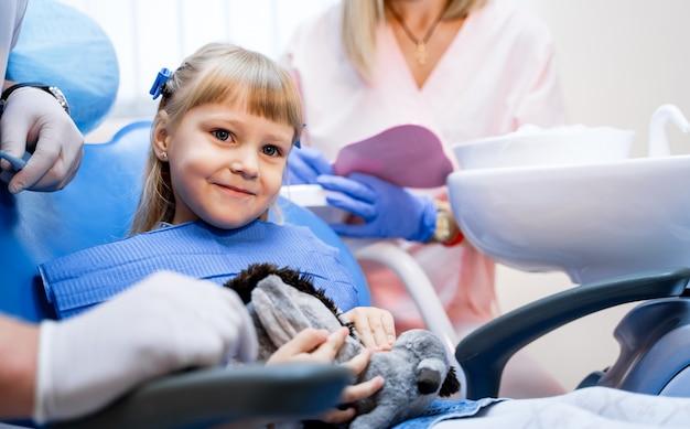 Close up van een klein schattig meisje, zittend met een gelukkige glimlach in stomatologie stoel