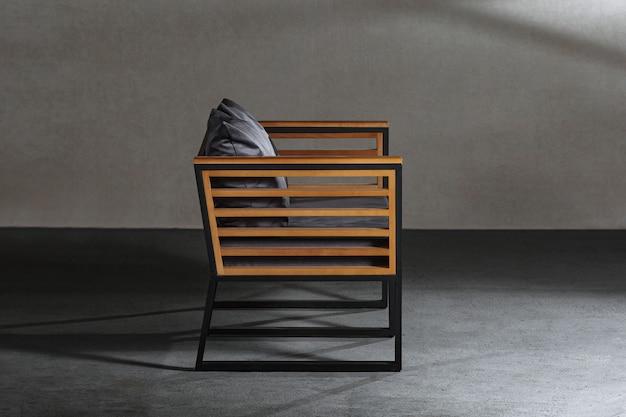 Close-up van een kleine houten stoel met een grijs kussen erop in een kamer