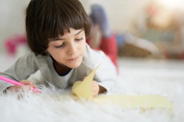 Close-up van een kleine latijns-jongen die geconcentreerd kijkt terwijl hij foto's maakt met kleurrijke potloden, liggend op de vloer. kind betrokken bij creatieve activiteit. afstandsonderwijs voor kinderen