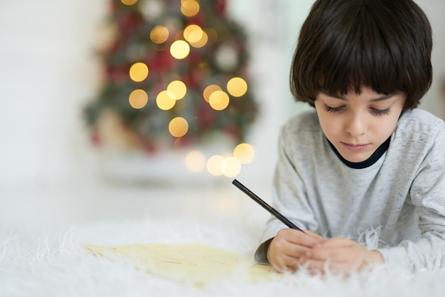 Close-up van een kleine latijns-jongen die geconcentreerd kijkt terwijl hij foto's maakt met kleurrijke potloden, liggend op de vloer thuis versierd voor kerstmis. kind betrokken bij creatieve activiteit