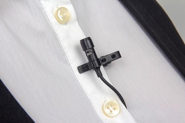 Close-up van een kleine lavalier-microfoon die met een klem aan een wit overhemd is bevestigd