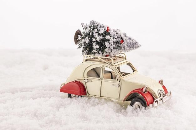 Close-up van een kleine vintage speelgoedauto met een kerstboom op het dak op een kunstmatige sneeuw