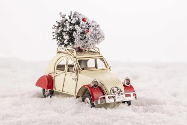 Close-up van een kleine vintage speelgoedauto met een kerstboom op het dak op sneeuw