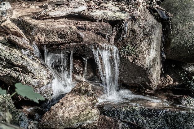 Close-up van een kleine waterval, omringd door rotsen onder het zonlicht overdag