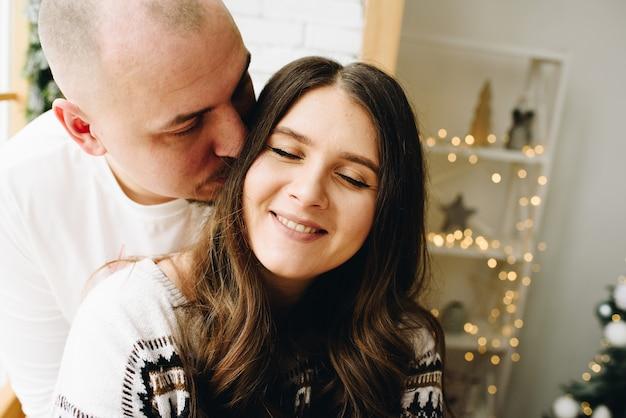 Close up van een knappe blanke man die zijn mooie vrouw kuste in de kamer versierd met lichten en slingers