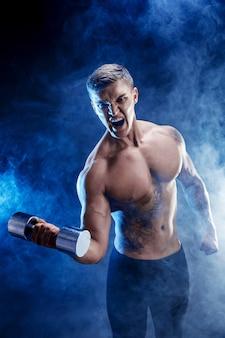 Close-up van een knappe bodybuilder die van de machts atletische mens oefeningen met domoor doen. geschiktheids gespierd lichaam op donkere rookachtergrond. perfecte reu. geweldige bodybuilder, tattoo, poseren.