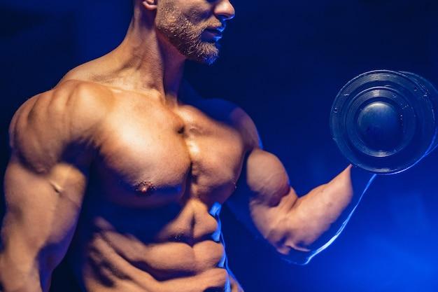 Close-up van een knappe bodybuilder die van de machts atletische mens oefeningen met domoor doet