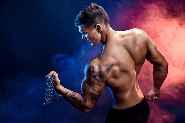 Close-up van een knappe bodybuilder die van de machts atletische mens oefeningen met ketting doen. fitness gespierd lichaam op donkere achtergrond. perfecte reu. geweldige bodybuilder, tattoo, poseren.