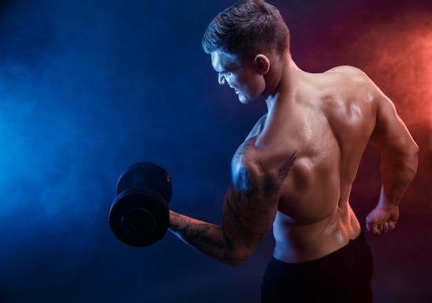 Close-up van een knappe bodybuilder van de machts atletische man die oefeningen met domoor doet fitness gespierd lichaam op donkere rookscène