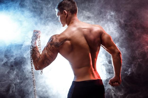 Close-up van een knappe bodybuilder van de machts atletische man die oefeningen met ketting doet fitness gespierd lichaam op donkere scène