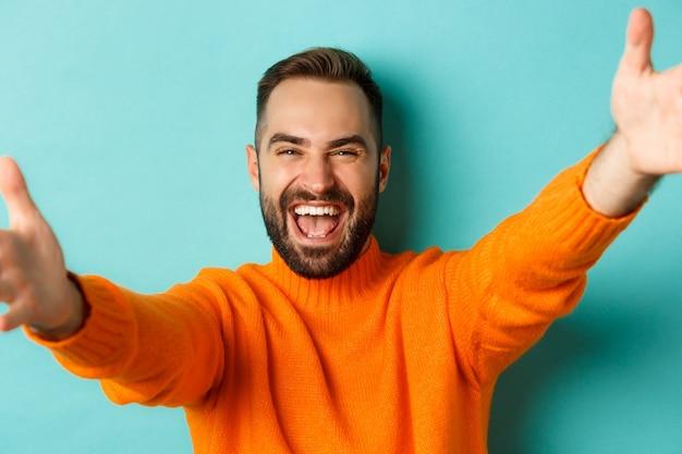 Close-up van een knappe, gelukkige man die zijn handen naar voren reikt en zijn armen uitstrekt voor een knuffel die tegen turkoois staat...
