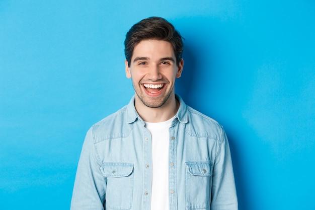 Close-up van een knappe jongeman die lacht, casual kleding draagt, over een blauwe achtergrond staat