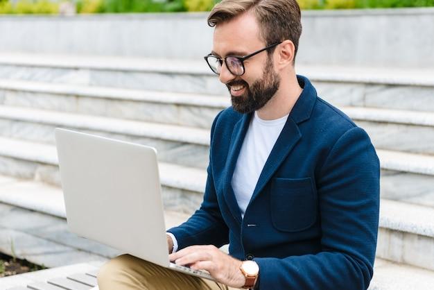 Close-up van een knappe lachende jonge bebaarde man met jas die op laptop werkt terwijl hij buiten zit op de stadsbank
