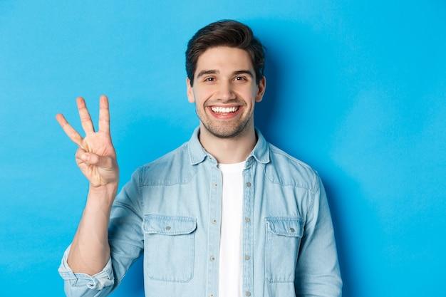 Close-up van een knappe man die lacht, vingers nummer drie toont, staande over een blauwe achtergrond