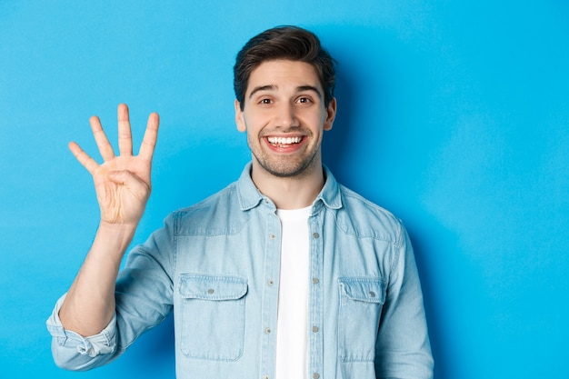 Close-up van een knappe man die lacht, vingers nummer vier toont, staande over een blauwe achtergrond.