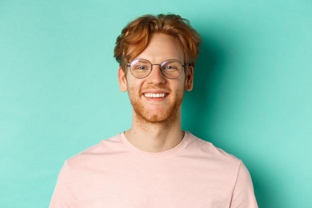 Close-up van een knappe roodharige man met een bril die naar de camera kijkt, glimlachend met witte tanden, staande tegen een mintachtergrond