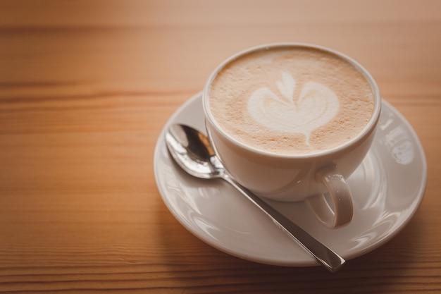 Close-up van een koffie latte op een houten vloer.