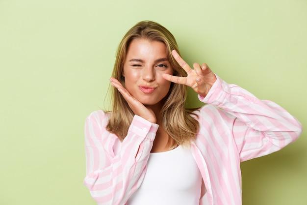 Close-up van een koket blond meisje in een roze shirt met vredesteken en knipogend gek staande over gr... Premium Foto