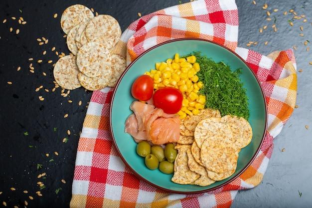 Close-up van een kom salade met zalm, crackers en groenten op een servet op tafel