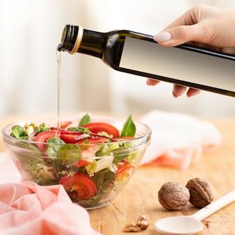 Close-up van een kom zomersalade en een mock-upfles notenboter in een vrouwelijke hand. olie wordt 1: 1 in salade gegoten