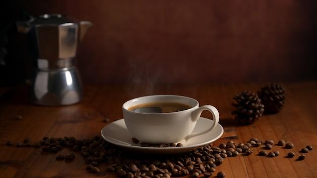 Close-up van een kopje koffie en koffiepot op houten tafel versierd met koffiebonen