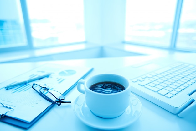 Close-up van een kopje koffie met een laptop en een bril