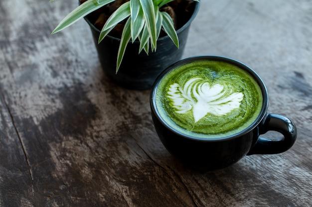 Close-up van een kopje matcha groene thee late art warme drank op houten tafel