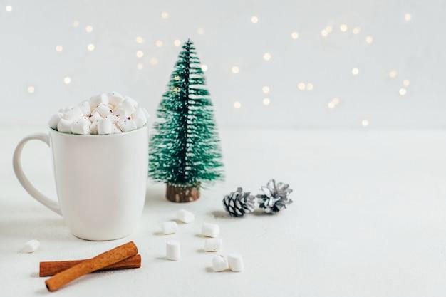 Close up van een kopje met cacao en mrashmallow op de achtergrond van een kerstboom van kegels van kaneelstokjes op een witte achtergrond