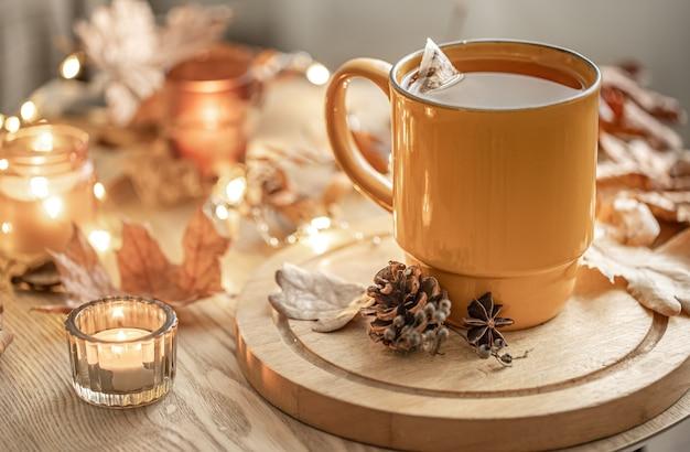 Close-up van een kopje thee tussen de herfstbladeren en kaarsen op een onscherpe achtergrond.