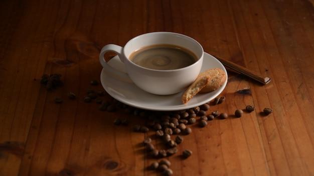 Close-up van een kopje warme koffie met koekje en koffiebonen ingericht op houten tafel