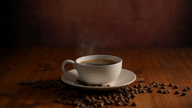 Close-up van een kopje warme koffie met koffiebonen ingericht op houten tafel