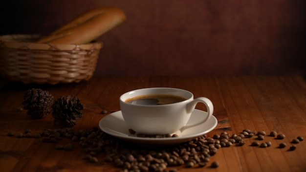 Close-up van een kopje warme koffie met stokbrood mand en koffiebonen op ontbijttafel