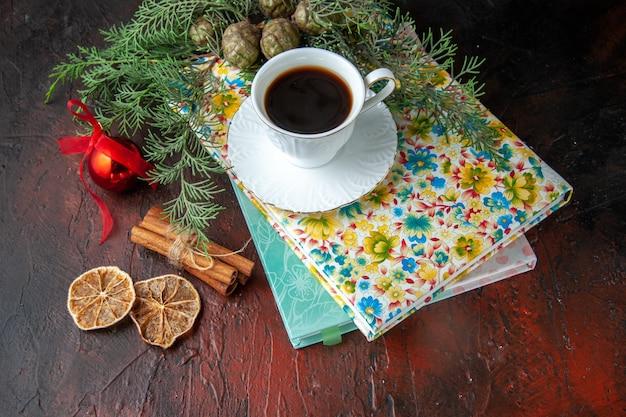 Close-up van een kopje zwarte thee op twee boeken, kaneellimoenen en dennentakken als decoratieaccessoire op donkere achtergrond