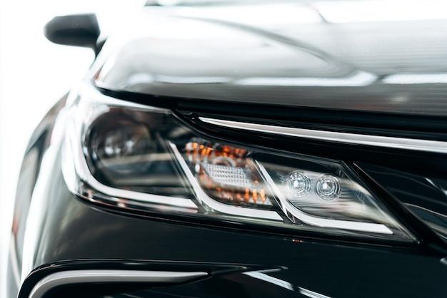 Close-up van een koplamp op een moderne zwarte auto met reflectie.
